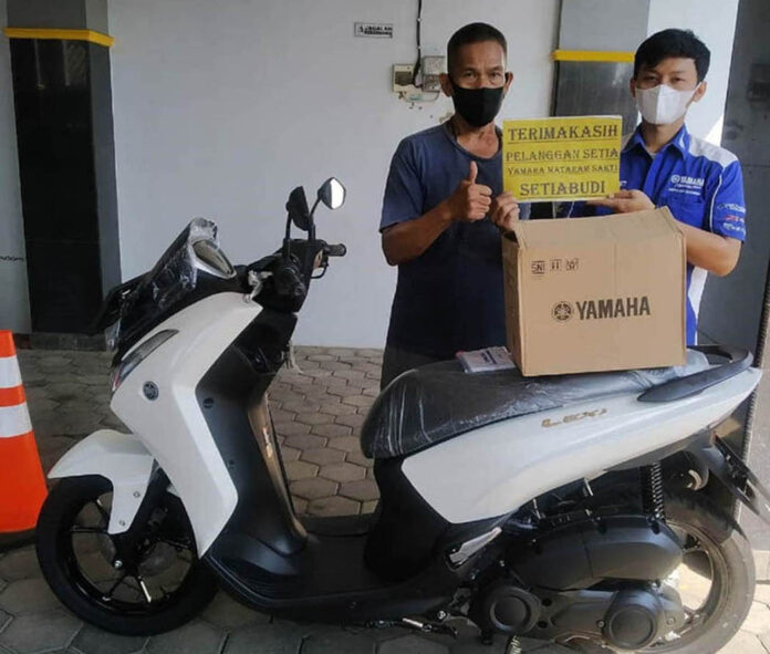 CASH.  Daniel Budi at the Yamaha Mataram Sakti Setiabudi dealer, Semarang, Central Java, when he bought a Yamaha Lexi 125 Standard motorcycle in cash using loose change that he had collected for one year and seven months.