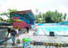 BERSIH-BERSIH. Salah satu pekerja di Pikatan Water Park sedang bersih-bersih sekitar kolam renang.