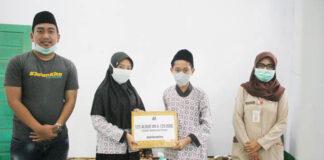 SERAHKAN. Founder #JalanKita OTW Lebih Baik, Gus Ahil (kiri) saat menyerahkan secara simbolis bantuan Iqro' dan Alquran, kemarin di Somongari Kecamatan Kaligesing.