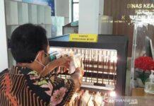 PERPUSTAKAAN. Seorang pengunjung Perpustakaan Umum Daerah Kabupaten Temanggung mengembalikan buku dengan memasukkannya ke boks sterilisasi dalam layanan tanpa sentuh (patuh).